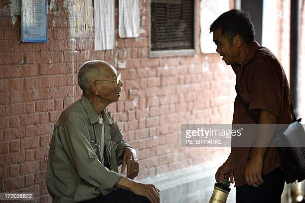 Elderly people talk on a street in Shanghai on July 1 2013 A Chinese law requiring family members to visit their elderly relatives went into effect...