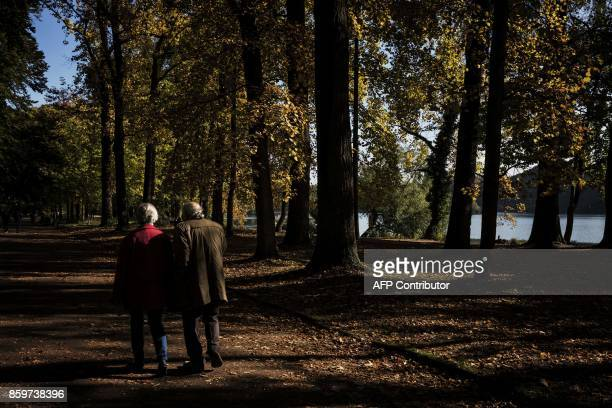 Elderly people walk on a path past trees in the Parc de la Tete d'Or on October 10 2017 in Lyon / AFP PHOTO / JEFF PACHOUD