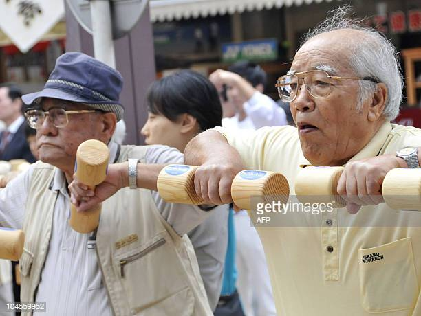 Elderly people work out with wooden dumbbells in the grounds of a temple in Tokyo on September 21 2009 to celebrate Japan's RespectfortheAgedDay The...