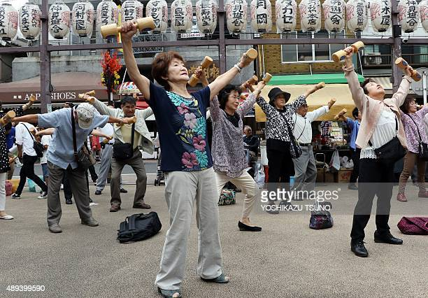 Elderly people work out with wooden dumbbells in the grounds of a temple in Tokyo on September 21 to celebrate Japan's Respect for the Aged Day The...