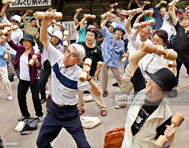 Elderly people workout with wooden dumbbells at the grounds of a temple in Tokyo 20 September 2004 to celebrate Japan's RespectfortheAgedDay The...