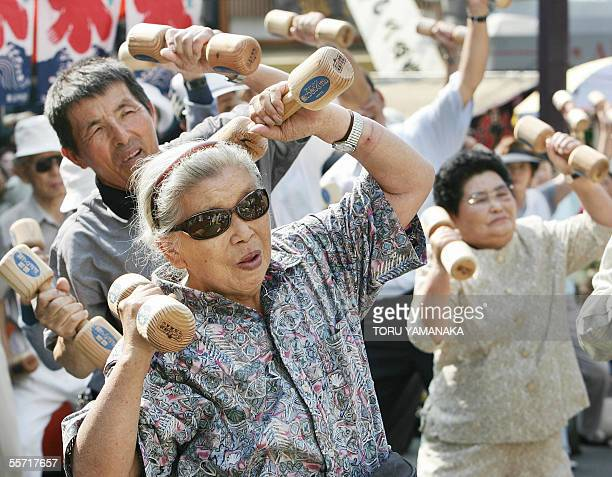 Elderly people workout with wooden weights at Koganji temple in Tokyo 19 September 2005 to celebrate Japan's RespectfortheAgedDay The government...
