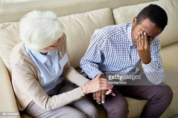 Elderly psychologist consoling patient