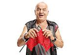 Elderly punker knitting and smiling isolated on white background