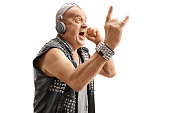 Elderly punker listening to music on headphones and making a rock hand gesture isolated on white background