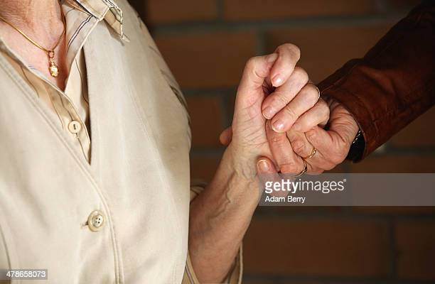 Elderly residents hold hands during the tenyear anniversary celebration of the Bestensee Senior Care Center on March 14 2014 in Bestensee near Berlin...