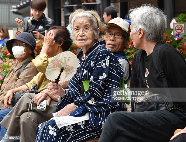 Elderly residents rest in the grounds of a temple in Tokyo on September 15 2014 as the country marks RespectfortheAgedDay The number of people aged...