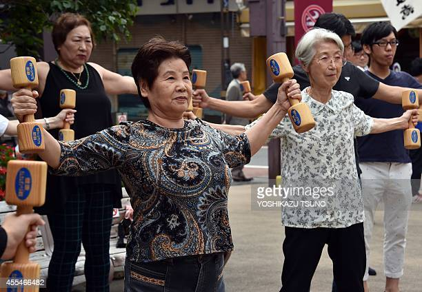 Elderly residents work out with wooden dumbbells in the grounds of a temple in Tokyo on September 15 2014 to celebrate Japan's RespectfortheAgedDay...