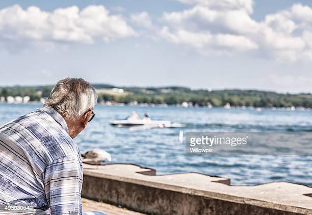 Elderly Senior Adult Man Admiring Lake Water Speed Boat