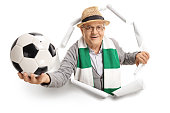 Elderly soccer fan with a scarf and a football breaking through paper