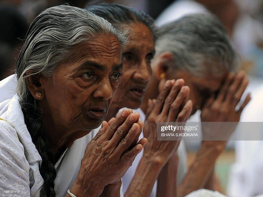 Elderly Sri Lankan Buddhists pray during Poya, a full moon religious festival, at the Kelaniya Temple in Kelaniya on December 27, 2012. The predominantly Buddhist Island nation marks every full moon as a key religious holiday. AFP PHOTO/ Ishara S. KODIKARA