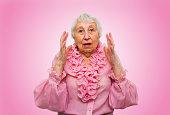 Elderly surprised woman on rose studio background