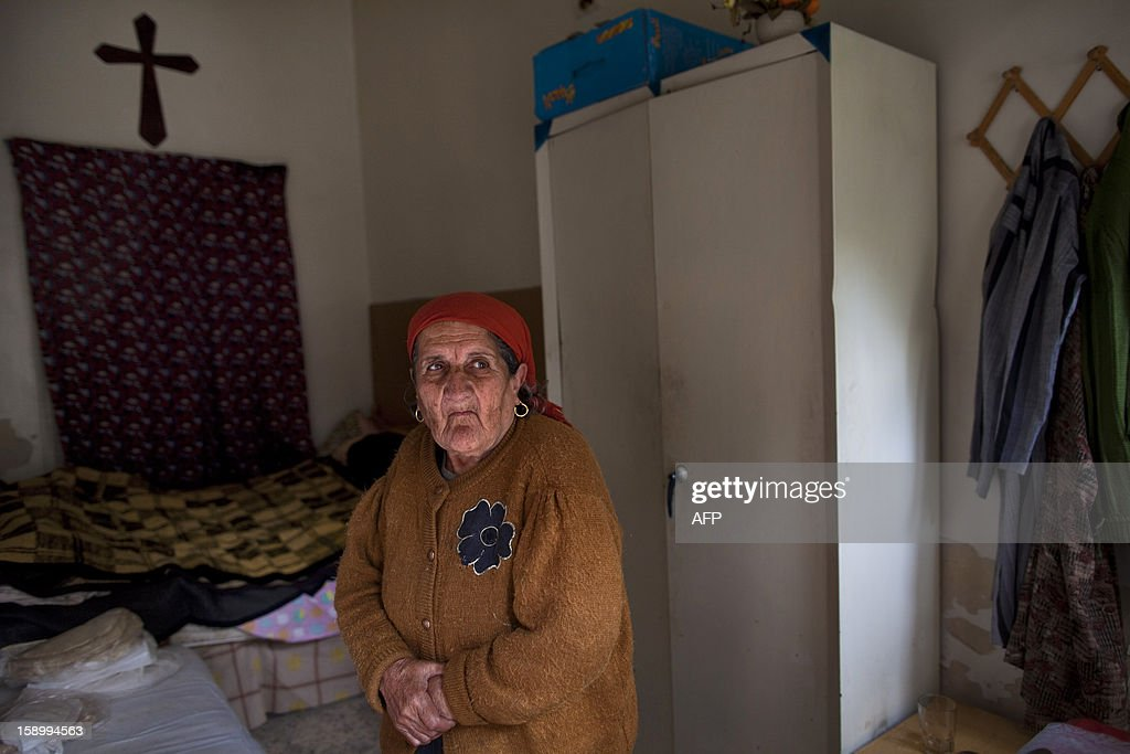 Elderly Syrian woman Adiba, 80, stands at her room in the St Elie Rest Home, founded in 1863, in Aleppo on January 02, 2013. The aging Christians holed up inside the retirement home in the devastated northern Syrian city of Aleppo have no light, no telephone lines, and little idea of what is happening in the outside world.