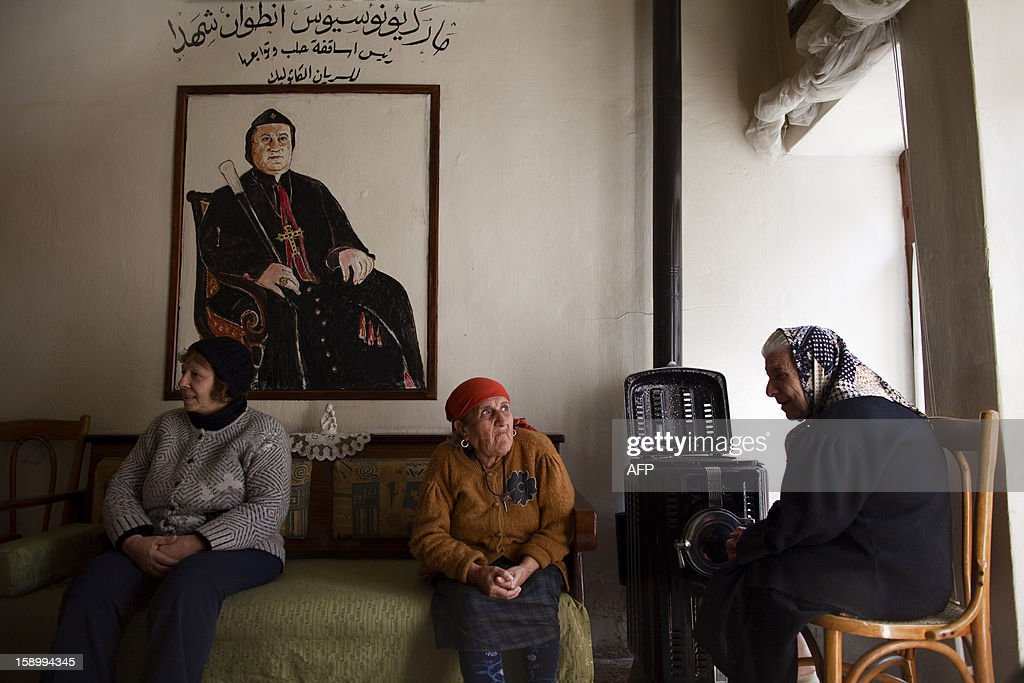 Elderly Syrian womem chat by the heater in the living room of the St Elie Rest Home, founded in 1863, in Aleppo on January 02, 2013. The ageing Christians holed up inside the retirement home in the devastated northern Syrian city of Aleppo have no light, no telephone lines, and little idea of what is happening in the outside world. AFP PHOTO/JM LOPEZ