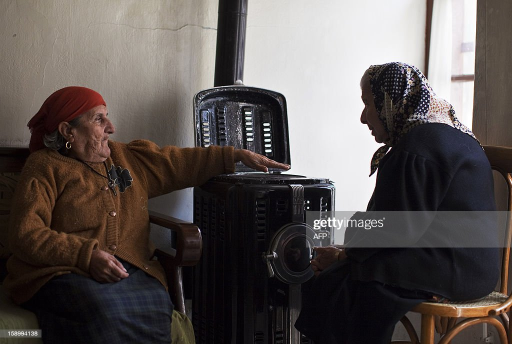 Elderly Syrian women, Adiba (L), 80, and Maggie (who doesn't know her age) chat by the heater in the living room of the St Elie Rest Home, founded in 1863, in Aleppo on January 02, 2013. The aging Christians holed up inside the retirement home in the devastated northern Syrian city of Aleppo have no light, no telephone lines, and little idea of what is happening in the outside world.