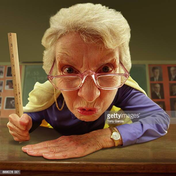 Elderly teacher with glasses, holding ruler, close-up (Composite)