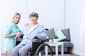 Photo of elderly woman with disability and caregiver
