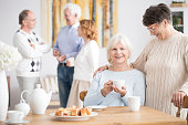 Elderly woman hugging smiling friend drinking tea during entertainment