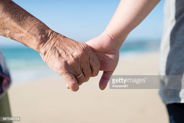 Elderly woman and young woman holding hands on the beach