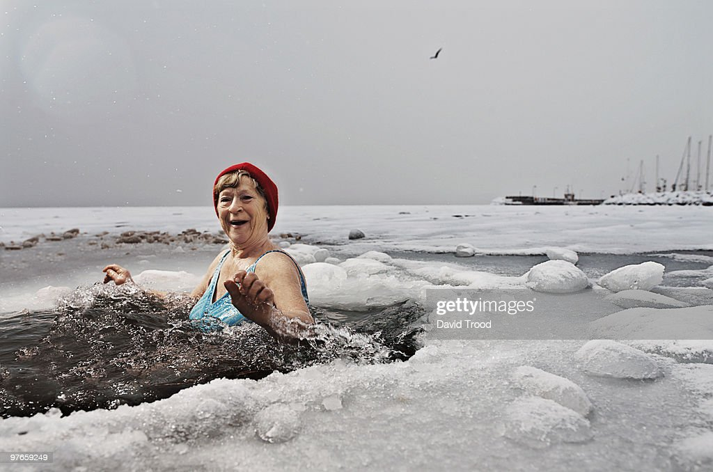 Elderly woman bathing in the frozen sea.
