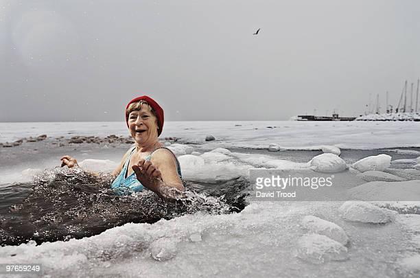 Elderly woman bathing in the frozen sea.