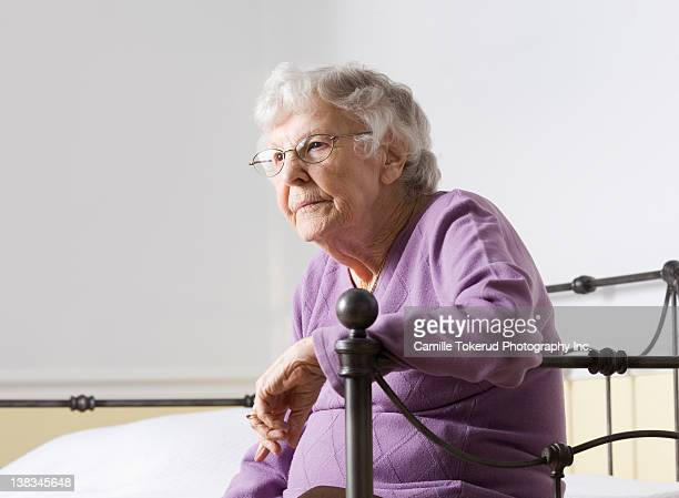 Elderly woman by the edge of bed thinking