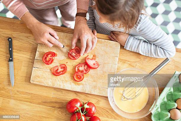 Elderly woman chopping tomatoes with her granddaughter in kitchen