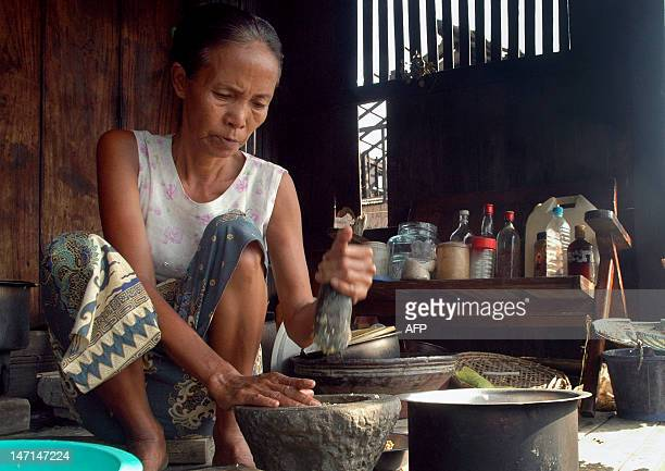 A elderly woman cooks meal for her family in Kungyangon in the outskirts of Yangon on May 8 2008 Myanmar's military rulers face mounting pressure to...