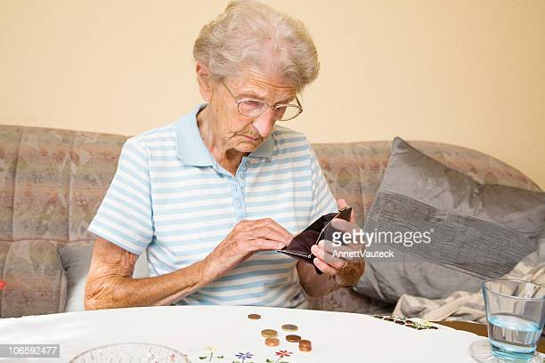 Elderly woman counting change from coin purse