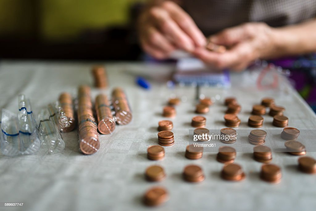 Elderly woman counting money, making stacks of Euro cents