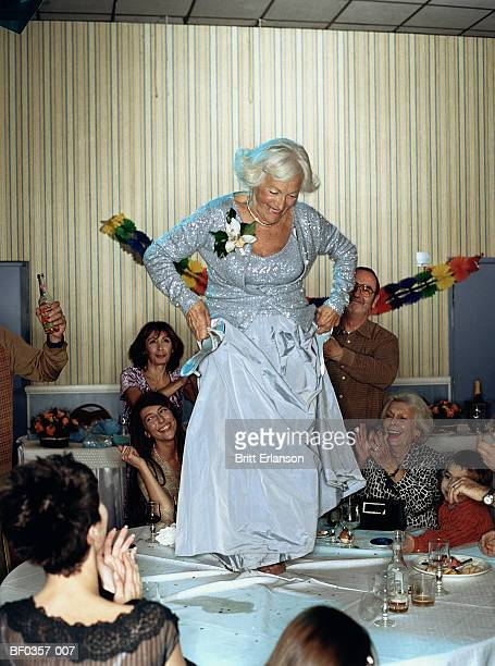 Elderly woman dancing on table surrounded by group of people