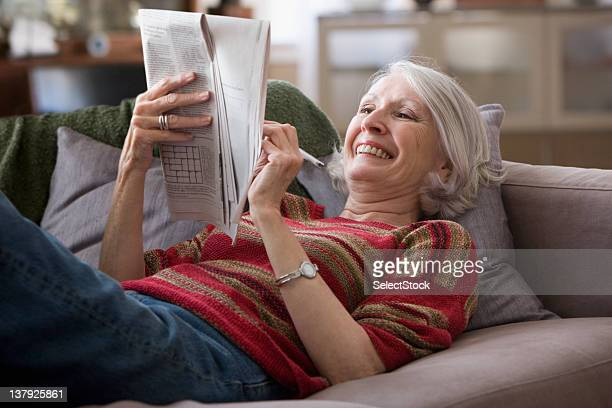 Elderly woman doing newspaper crossword puzzle