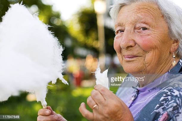 Elderly woman eating cotton candy at a fair