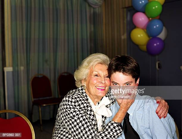 Elderly woman embracing teenage boy (13-15), portrait
