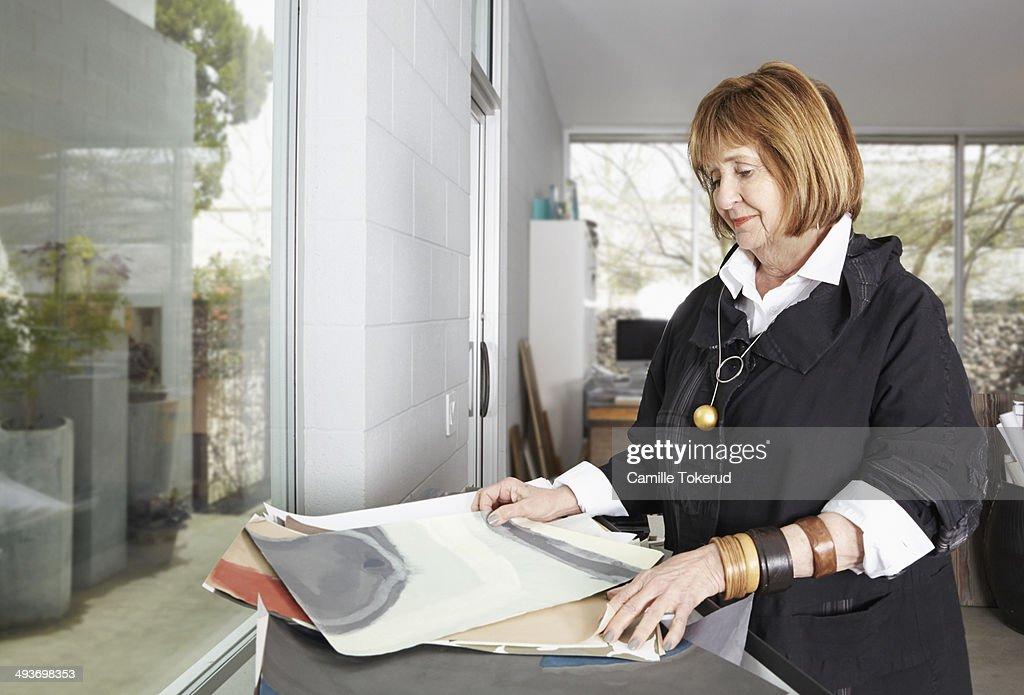 Elderly woman holding design drawings : Stock Photo