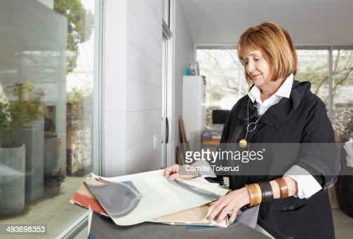 Elderly woman holding design drawings : Stock Photo