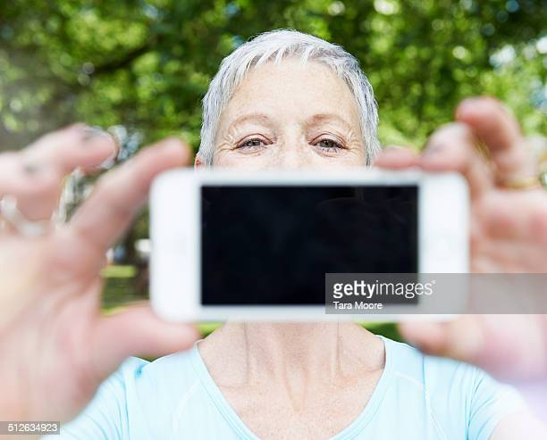elderly woman holding up smart phone in park