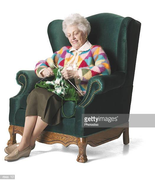 Elderly woman in a colorful sweater knits.