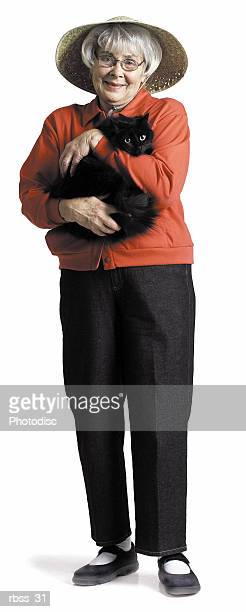 Elderly woman in a red shirt and a straw hat smiling at the camera holding a cat