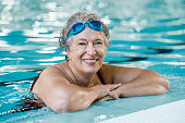 Mature woman wearing swim goggles at swimming pool. Fit active senior woman enjoying retirement standing in swimming pool and looking at camera. Happy senior healthy old woman enjoying active lifestyl