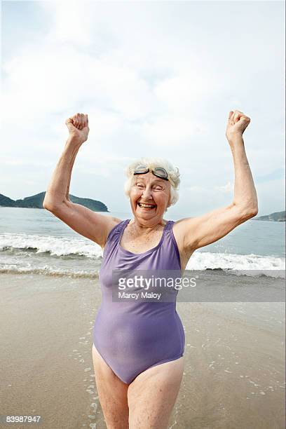 Elderly woman in swimsuit and goggles on beach.