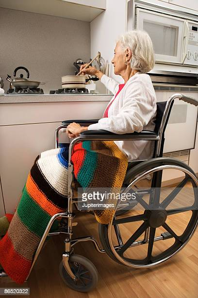 Elderly woman in wheelchair cooking