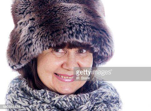 Elderly woman in winter fir hat and wool scarf : Stock Photo