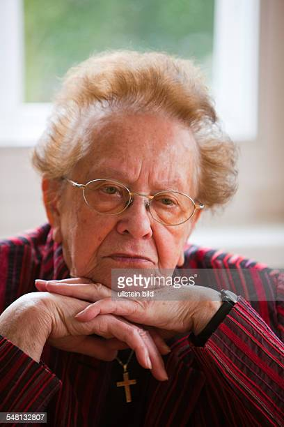 elderly woman is contemplative and apprehensive