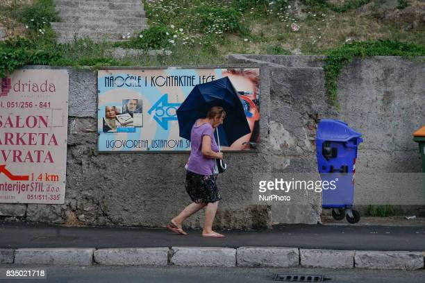 A elderly woman is seen walking in the center of Rijeka Croatia during a sudden rainstorm on 24 July 2017