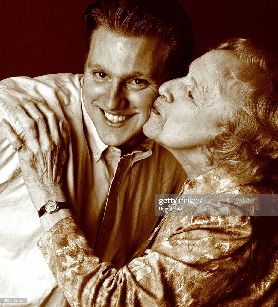 Elderly woman kissing young man on cheek, close-up (Enhancement) : Stock Photo