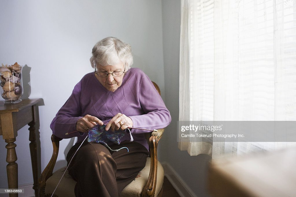 Elderly woman knitting at home