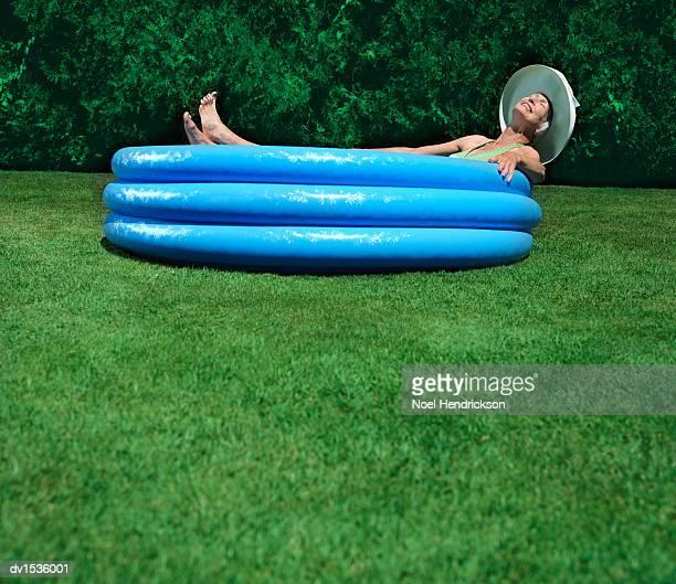 Elderly Woman Lies in a Paddling Pool on Green Grass, Sunbathing