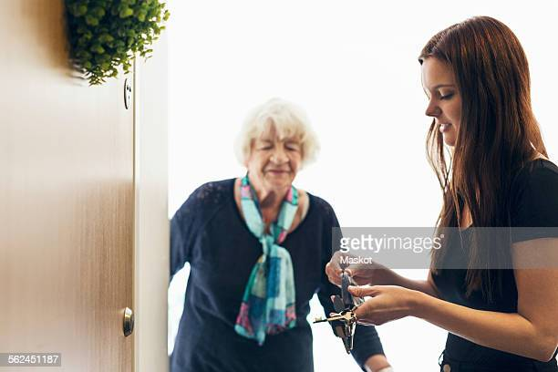 Elderly woman looking at granddaughter unlocking front door of house