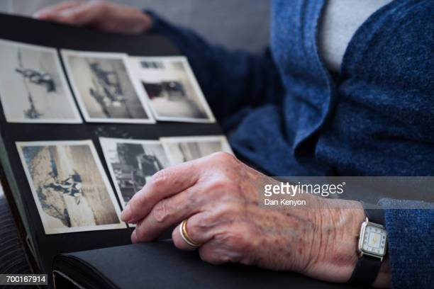 Elderly woman looking at old fashioned photograph album